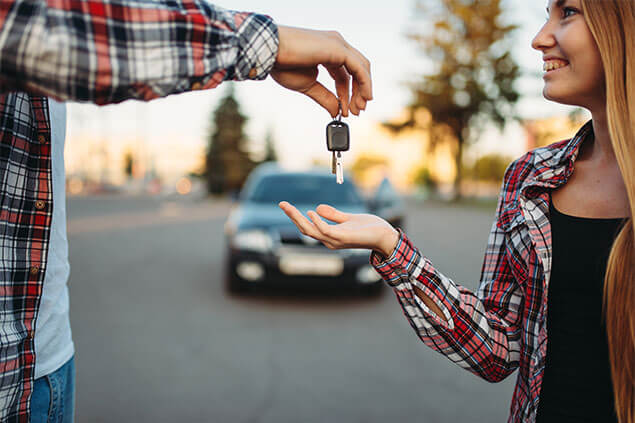 A faceless person hands keys to young woman