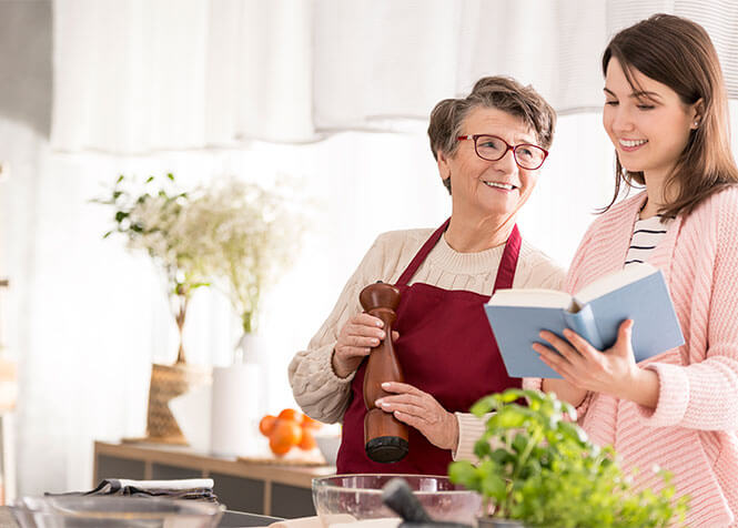 Young and old ladies cooking together and smiling