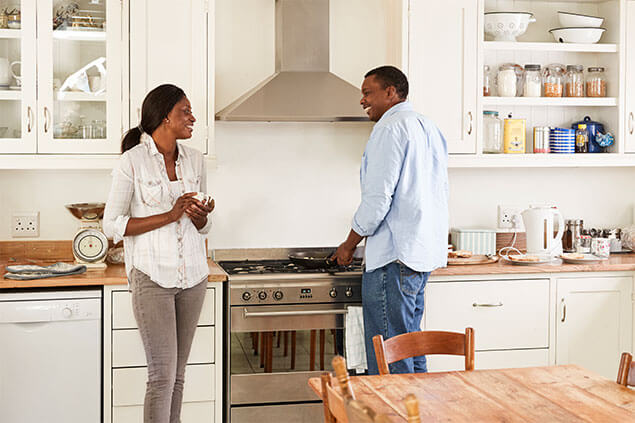 Mature couple standing in their kitchen cooking and chatting