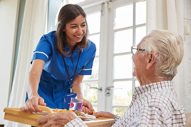 Nurse giving senior citizen food
