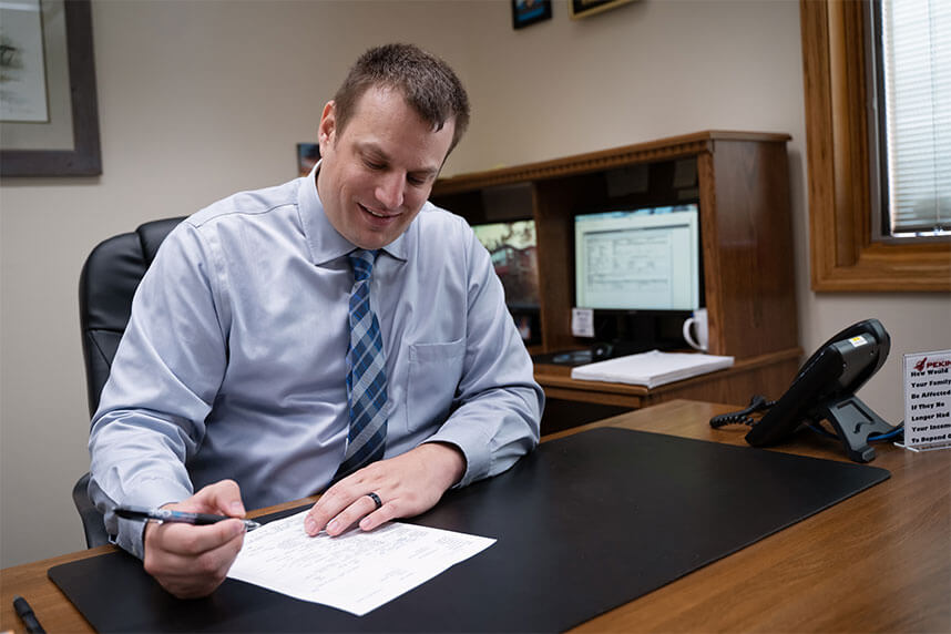 Insurance man working at brown desk writing things on some paper